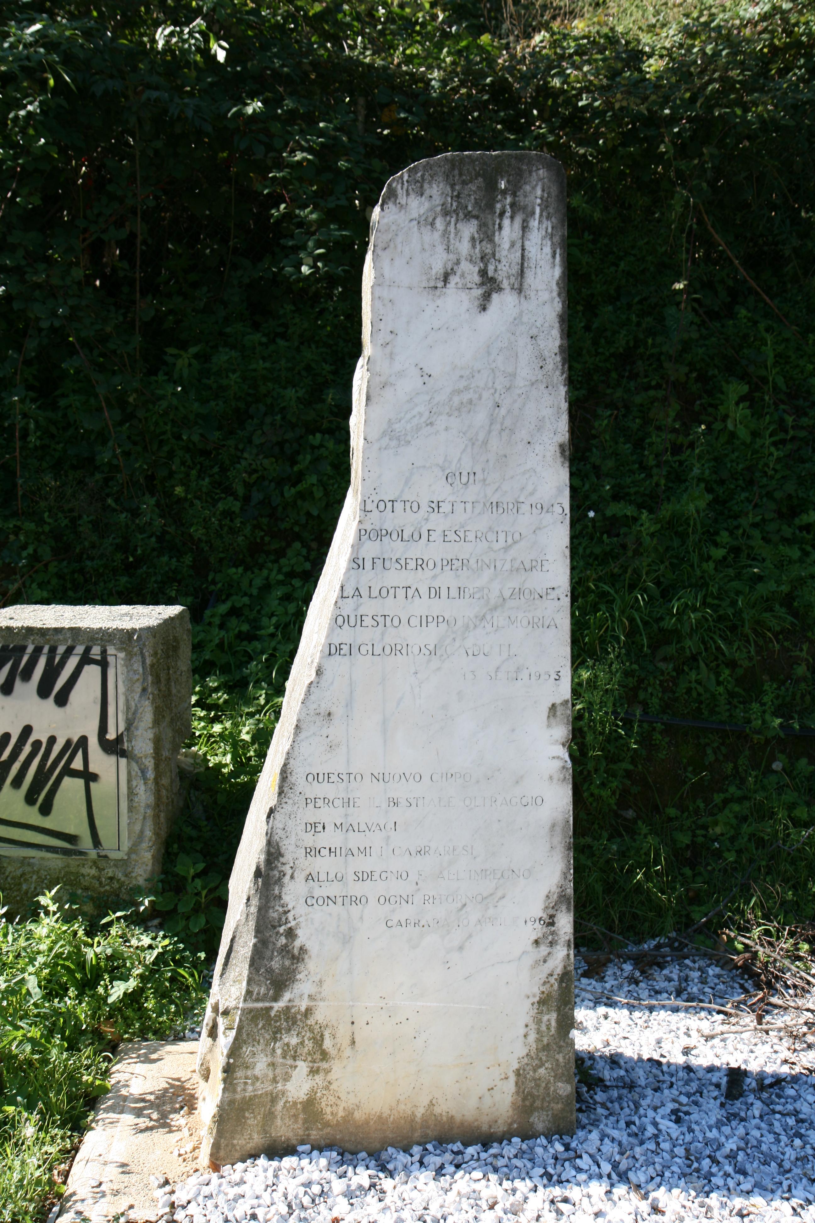 Epigrafe: QUI L'OTTO SETTEMBRE 1943 POPOLO E ESERCITO SI FUSERO PER INIZIARE LA LOTTA DI LIBERAZIONE QUESTO CIPPO IN MEMORIA DEI GLORIOSI CADUTI. 13 SETTEMBRE 1953. La seconda parte dell'epigrafe reca memoria dell'atto vandalico che distrusse questo monumento alla resistenza partigiana QUESTO NUOVO CIPPO PERCHÉ IL BESTIALE OLTRAGGIO DEI MALVAGI RICHIAMI I CARRARESI ALLO SDEGNO E ALL'IMPEGNO CONTRO OGNI RITORNO CARRARA 10 APRILE 1965
