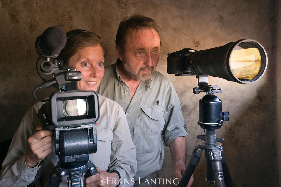 Christine Eckstrom and Frans Lanting in wildlife observation bunker at water hole, Etosha National Park, Namibia