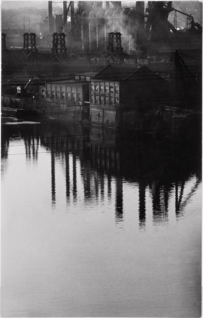 MAST: fotografia di Eugene Smith. Città industriale riflessa sull'acqua